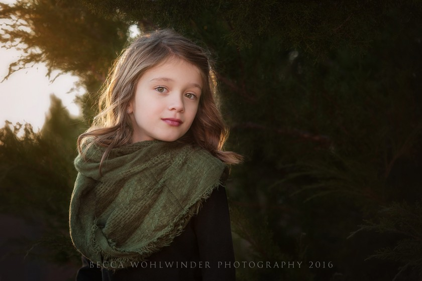 portrait of young girl by trees by Becca Wohlwinder