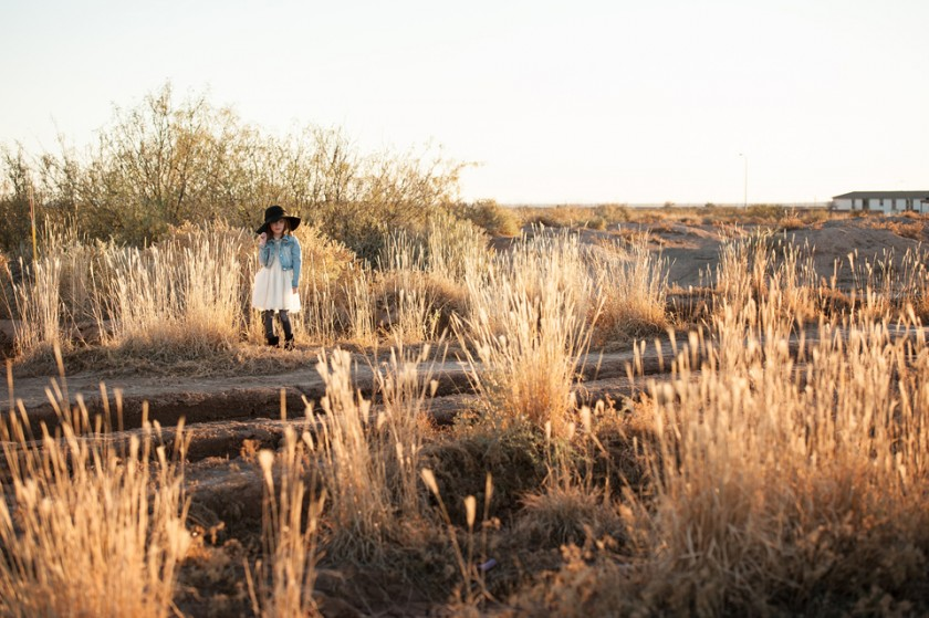pullback photo of girl in a hat standing in the grass by Becca Wohlwinder