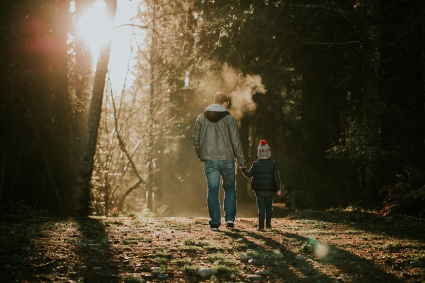 backlit photo of dad and son walking through the trees by Cassandra McCasley of Twist and Shutter Photography