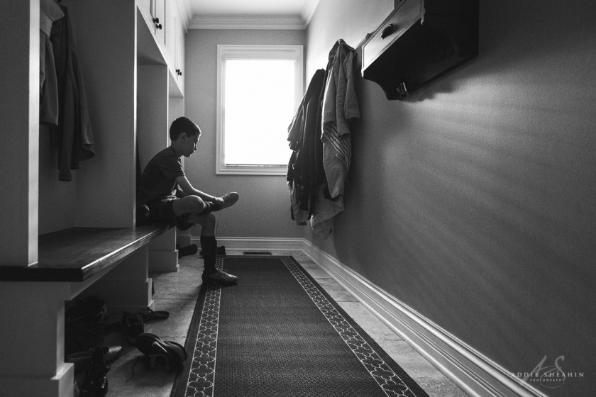 black and white photo of boy putting on his cleats by Addie Sheahin