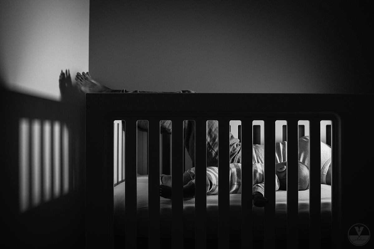 black and white photo of child sleeping in crib by Vironica Golden