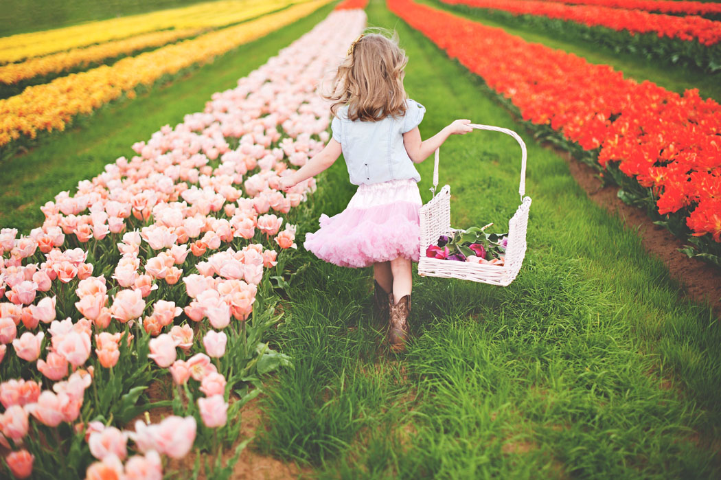 girl in a tutu and cowboy boots walking through a tulip field by Erica Williams of Woodsy Wonders Photography