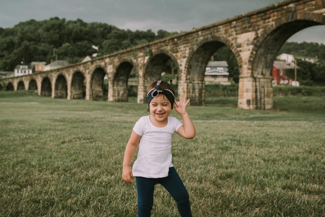 girl smiling in a field by Kaela Elliott