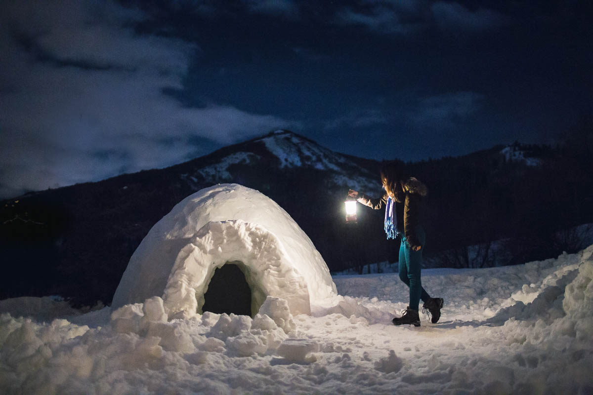 photo of woman holding a lantern by an igloo by Alice Che