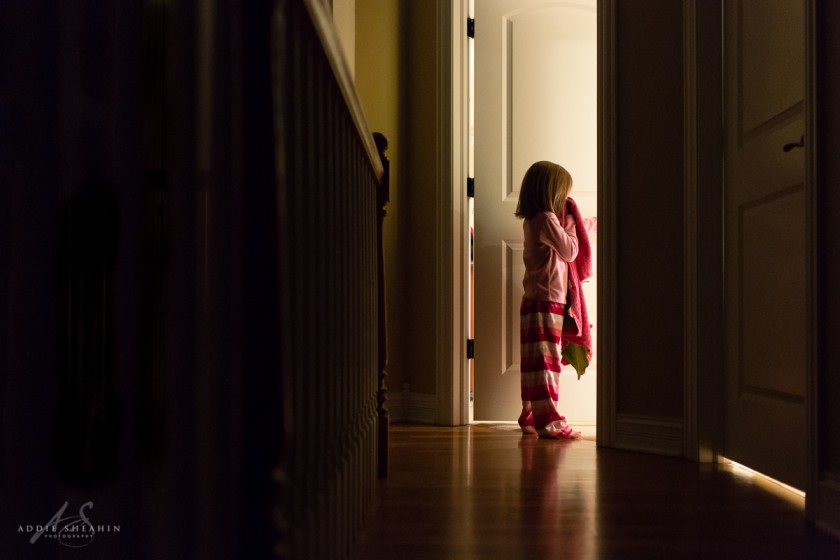 picture of girl holding a blanket and opening a bedroom door by Addie Sheahin