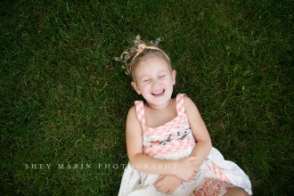 picture of girl laying in the grass and laughing by Shey Detterline