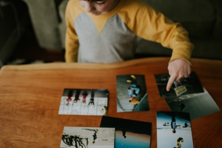 picture of kid looking at printed photos by Cassandra McCasley of Twist and Shutter Photography