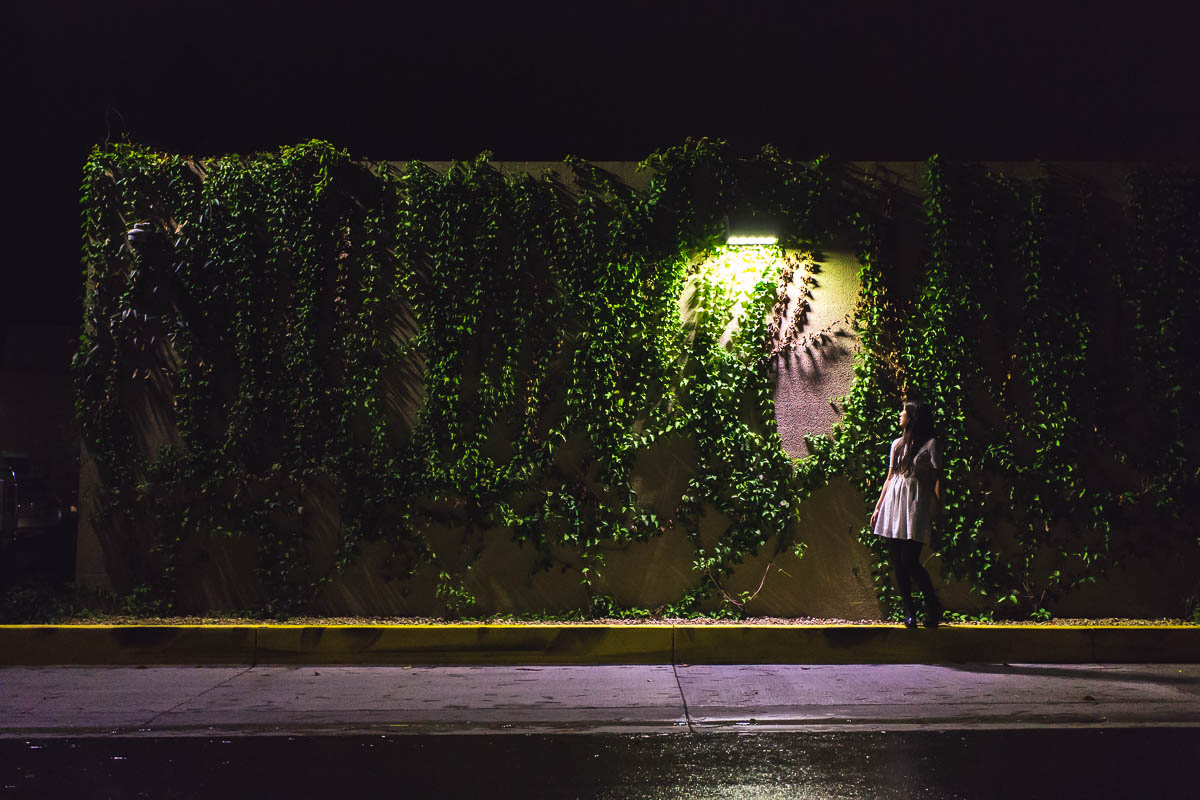 picture of woman standing by a wall of ivy at night by Alice Che
