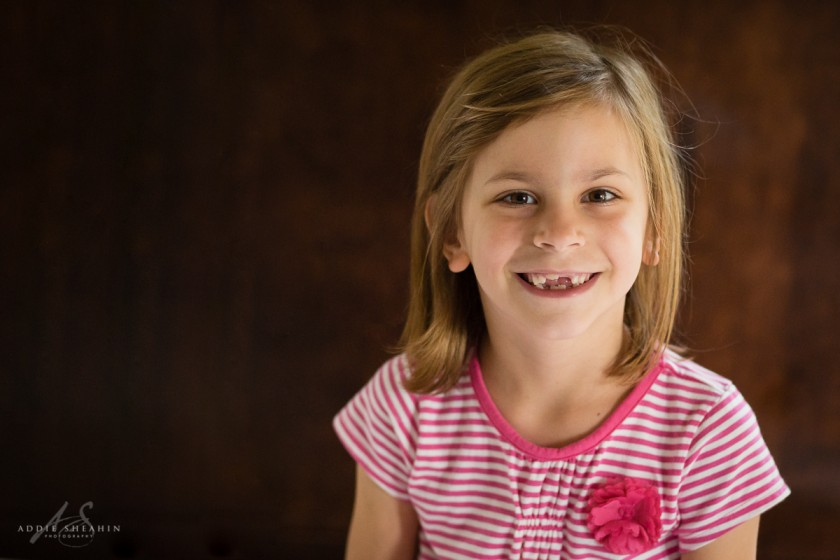 portrait of girl in striped shirt smiling by Addie Sheahin