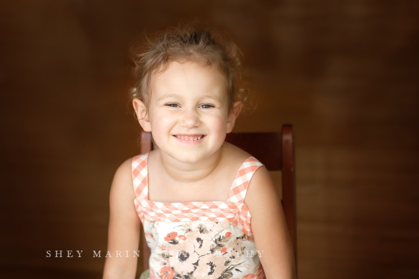 portrait of girl sitting in a chair and smiling by Shey Detterline