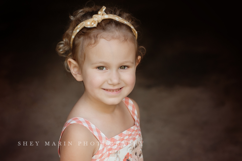 portrait of girl with curly hair taken in a garage by Shey Detterline