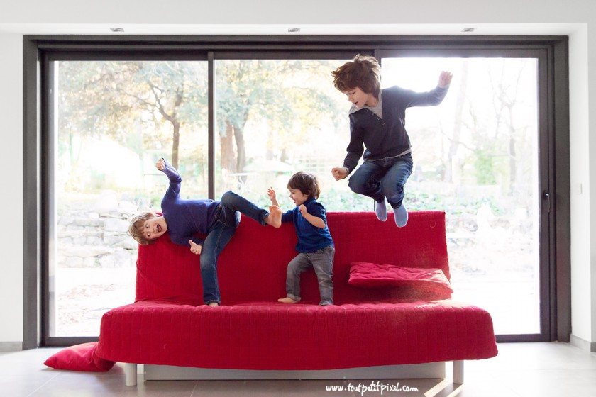 3 boys jumping on a red couch by Lisa Tichane 2