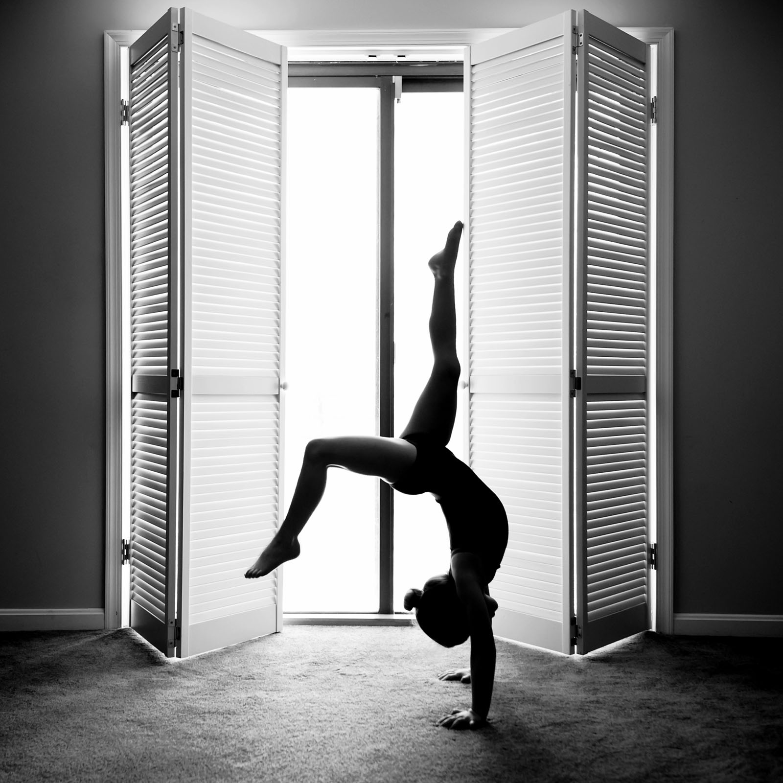 backlit photo of a young girl doing a handstand by Allison McSorley
