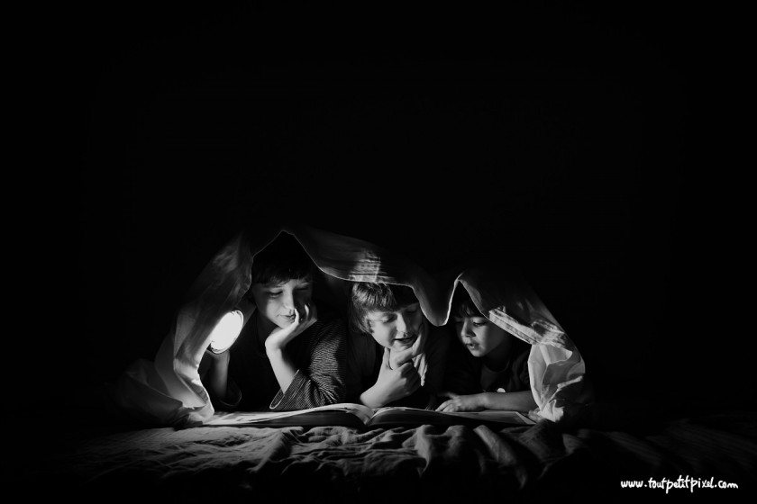 black and white photo of brothers reading with a flashlight by Lisa Tichane