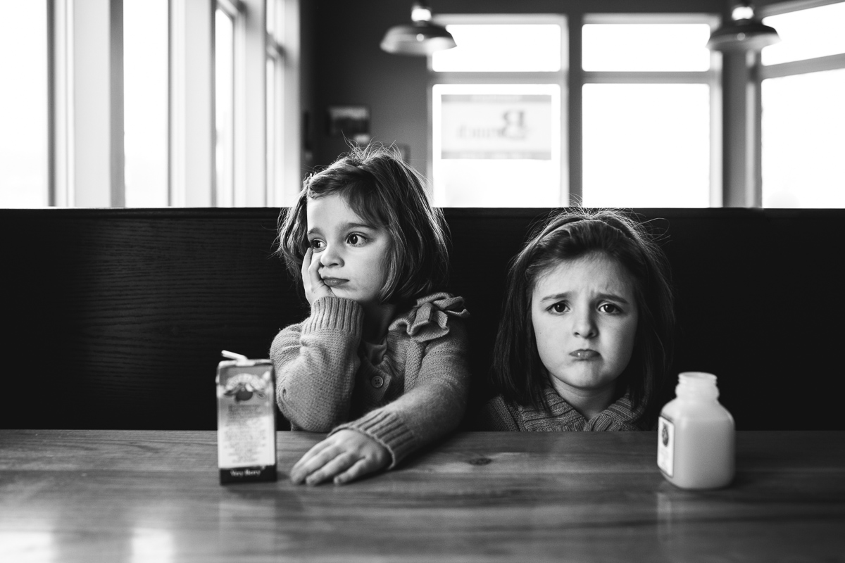 black and white photo of sisters drinking juice by Kristy Dooley