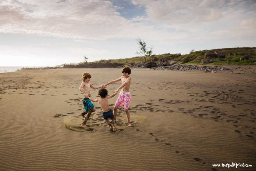 brothers holding hands and playing on the beach by Lisa Tichane 5
