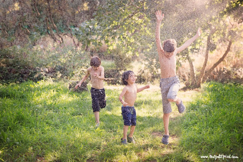 photo of 3 boys playing in a water sprinkler by Lisa Tichane 4