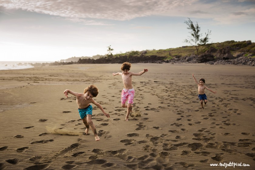 photo of 3 boys running on the beach by Lisa Tichane