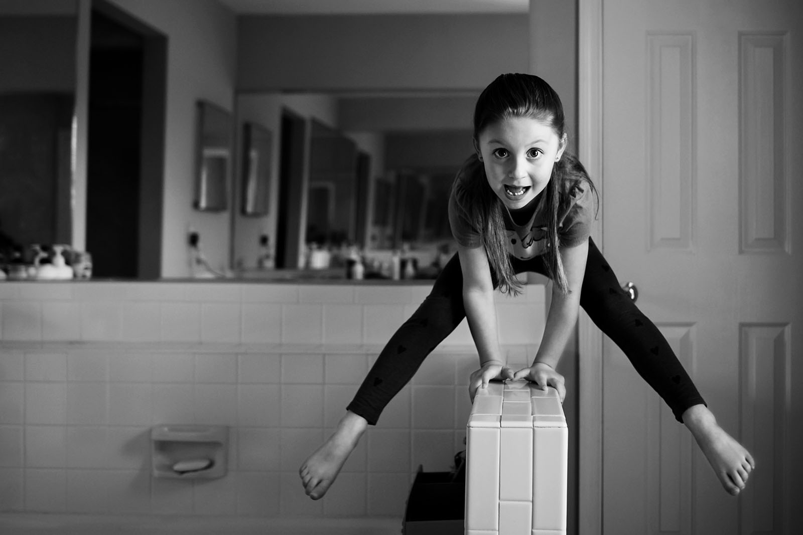 photo of child doing gymnastics in the bathroom by Allison McSorley