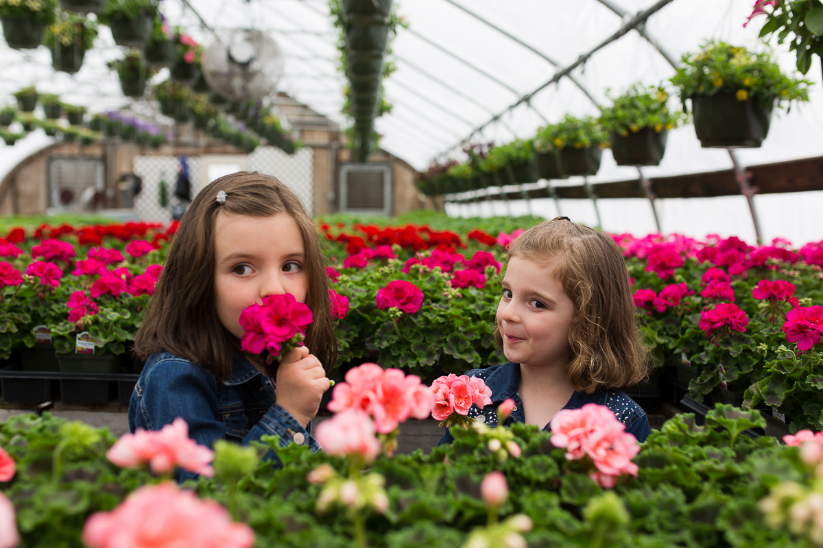 photo of sisters smelling flowers by Kristy Dooley