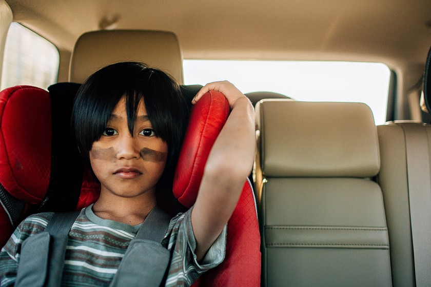 pic of young boy sitting in a red carseat by Winnie Bruce