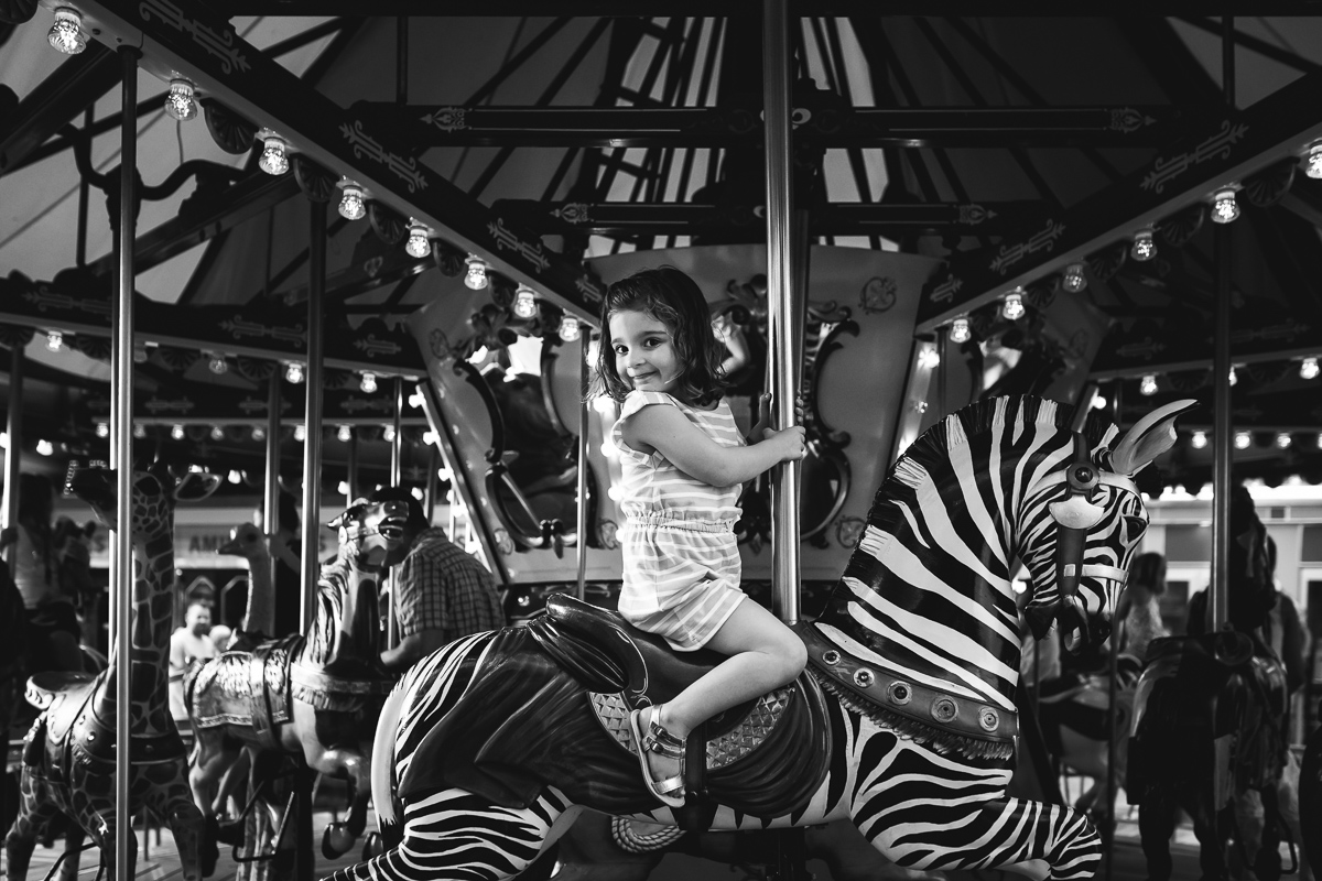 picture of a girl riding a zebra on a carosuel by Kristy Dooley