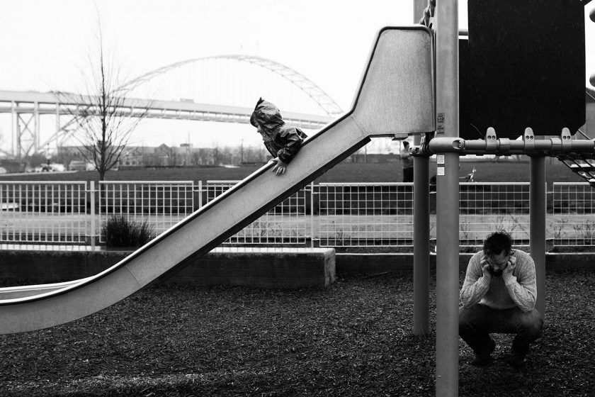 black and white photo of boy sliding by Lacey Monroe