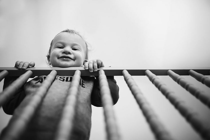 black and white photo of kid looking out of crib by Kellie Bieser