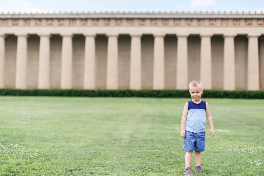 boy standing in the grass by the Parthenon by Leanne Vice
