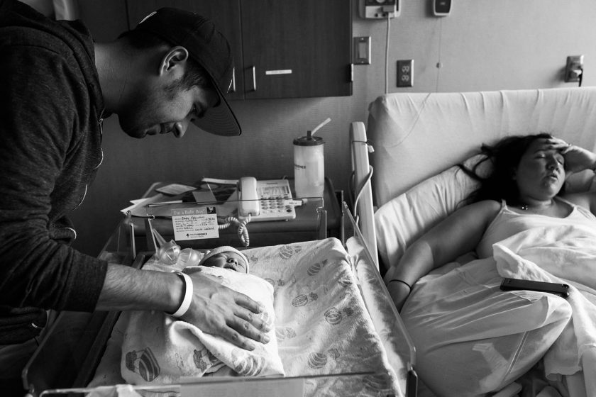 hospital picture of dad looking at newborn by Lacey Monroe