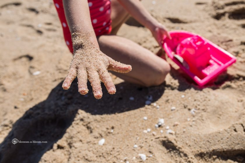 kids hand covered in sand by Annmarie Kopey 7