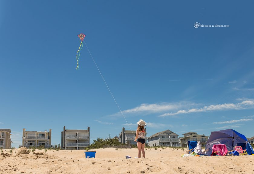photo of girl flying a kite on the beach by Annmarie Kopey