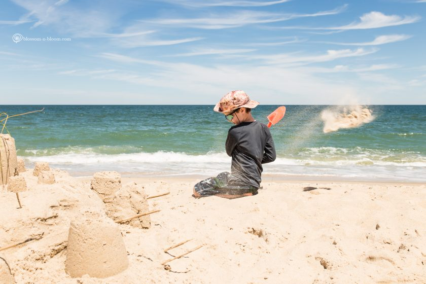 picture of boy diggin on the beach by Annmarie Kopey