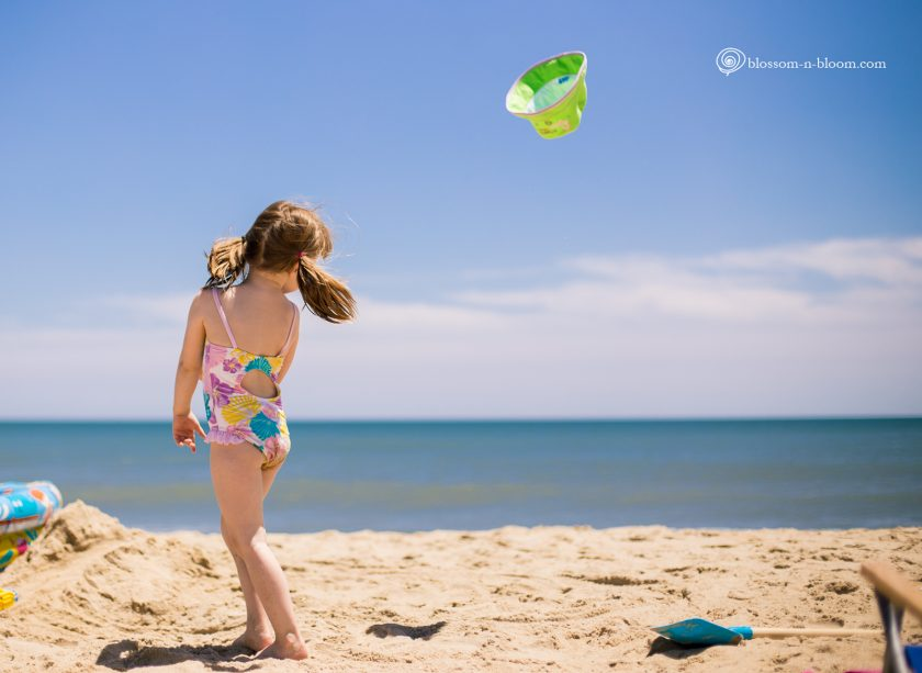 picture of girl throwing her hat on the beach by Annmarie Kopey