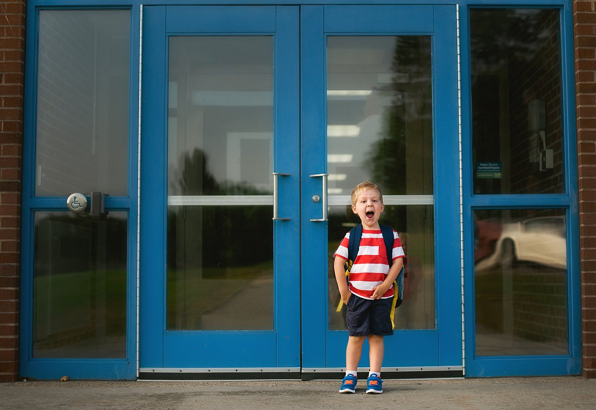 colorful photo of little boy on the first day of schoold by Beth Mancuso