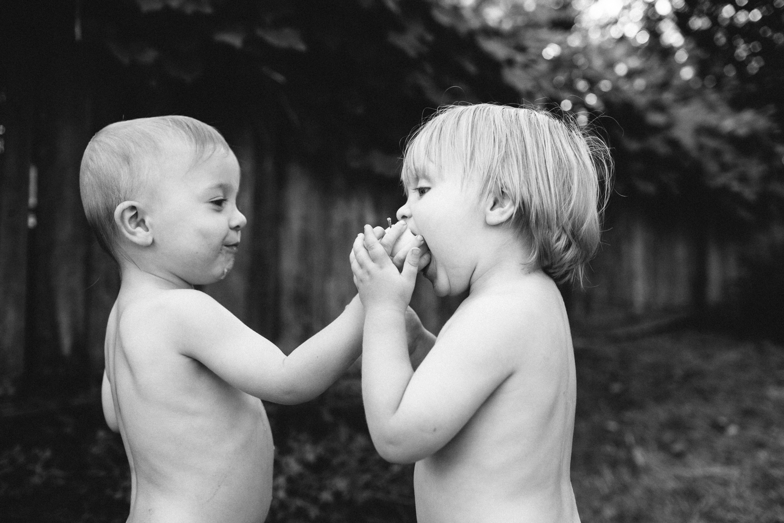 black and white photo of two boys sharing an apple by Meghan McMackin