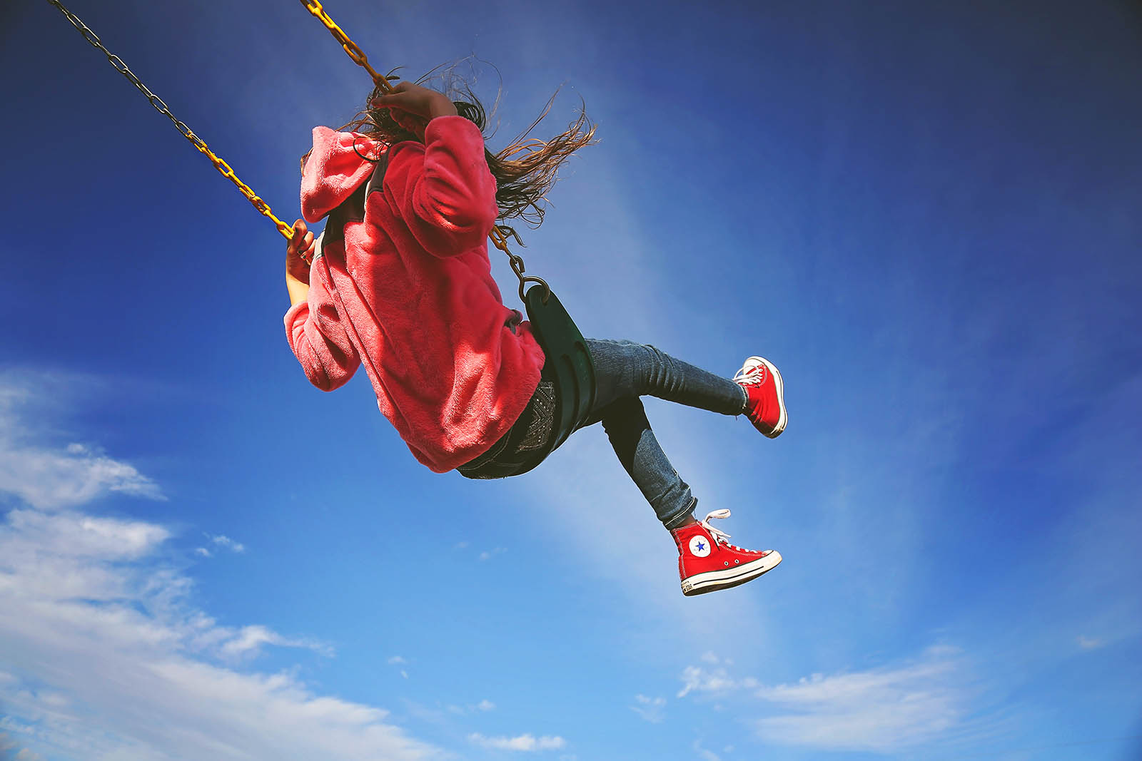 photo of girl in a red sweatshirt swinging by Michelle Stoddard