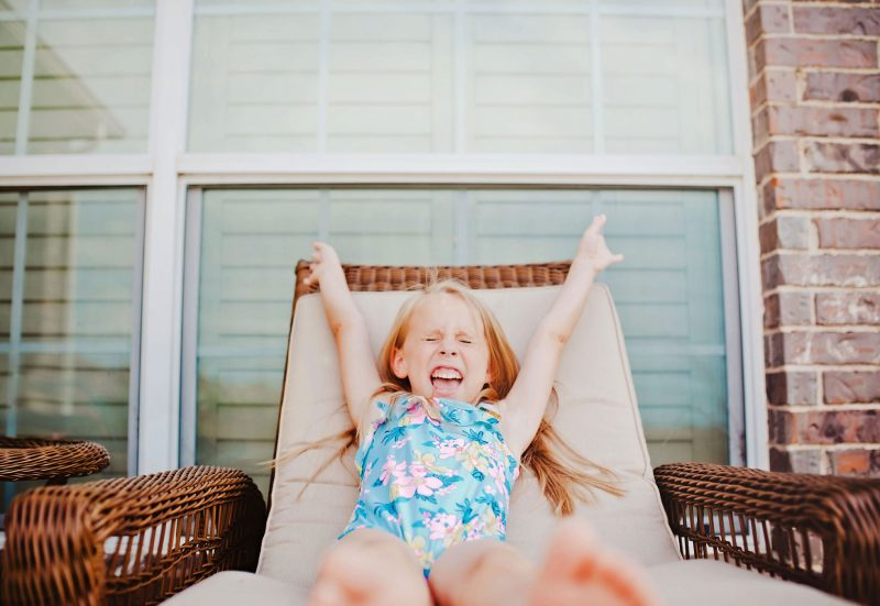 photo of girl raising her arms by Erica Williams of Woodsy Wonders