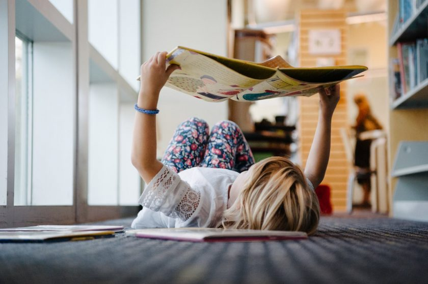 picture of girl reading a book on the floor by Danielle Hatcher
