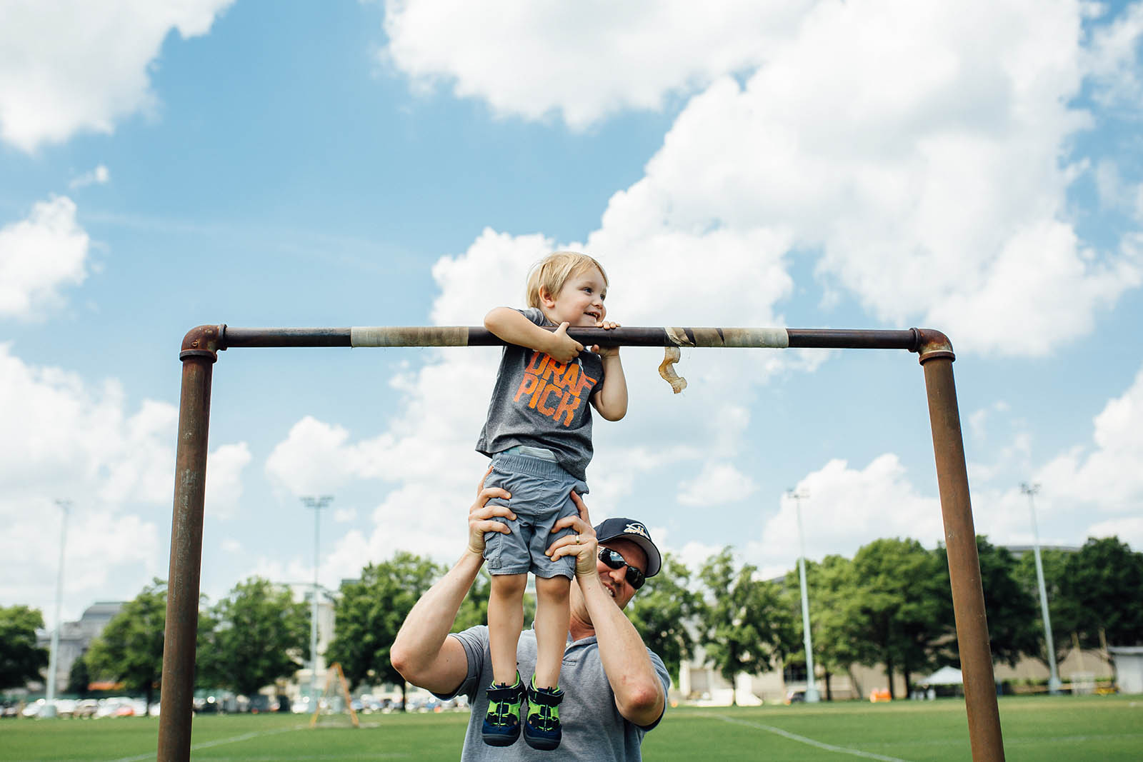 picture of kid hanging on poles on a football field by Michelle Stoddard