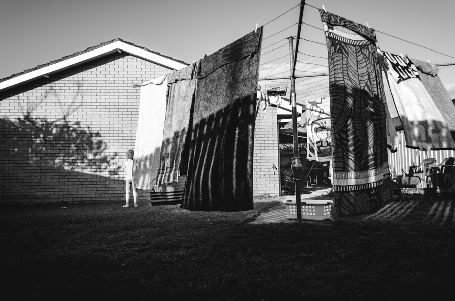 environmental-clothesline-scene-unexpectedly-reveals-child-in-black-and-white-creative-portrait-by-photographer-katy-bindels