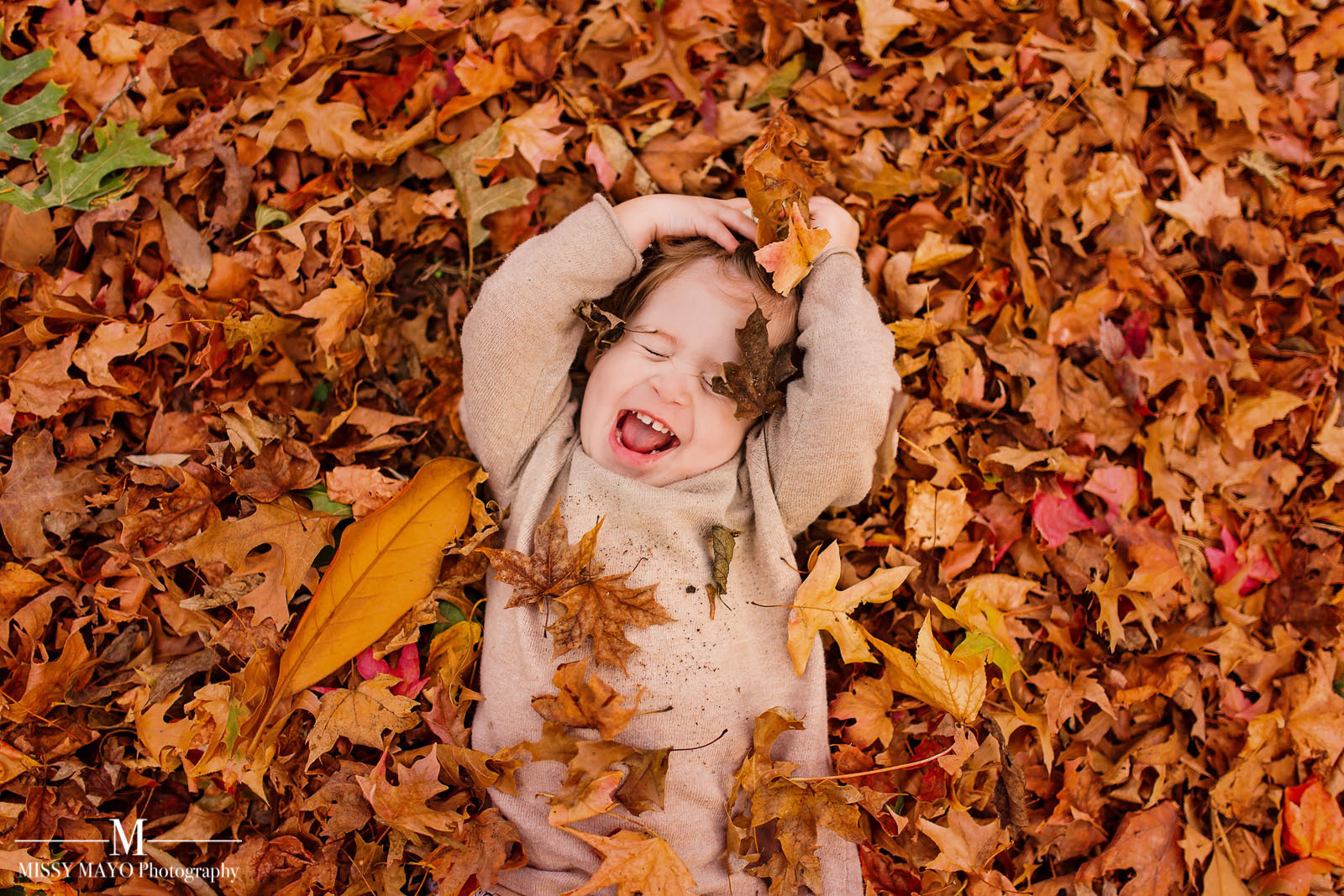 baby in a leaf pile by Missy Mayo