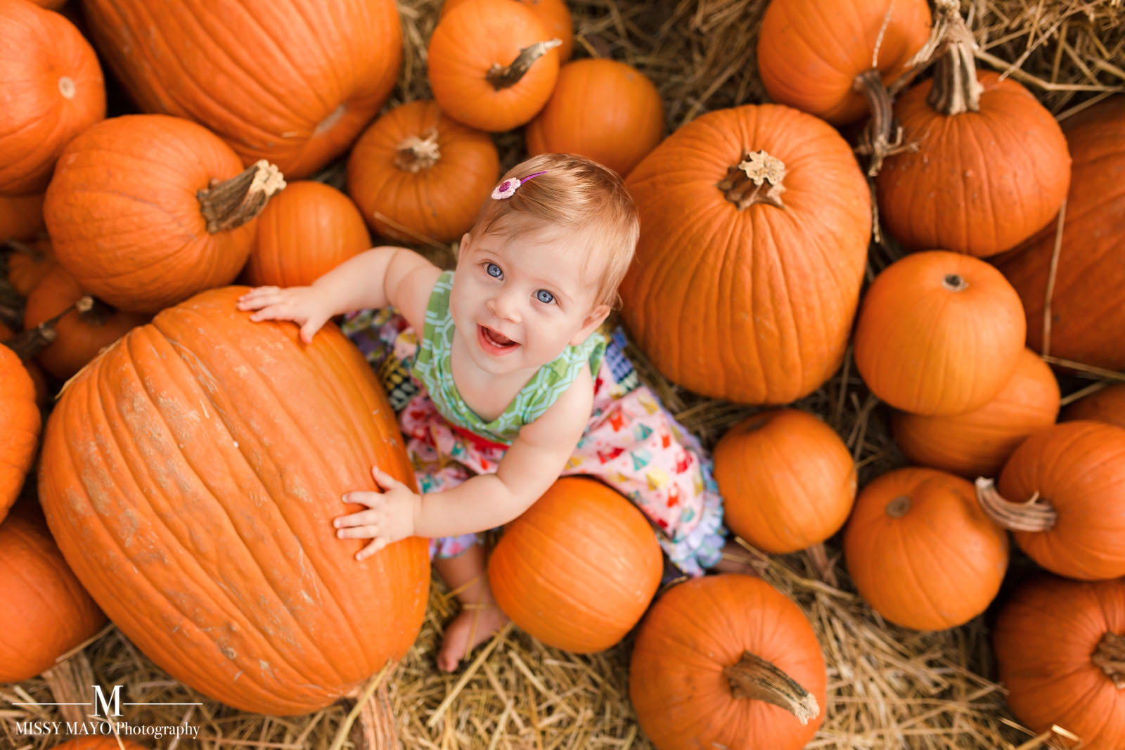 baby sitting in a pile of pumpkins by Missy Mayo