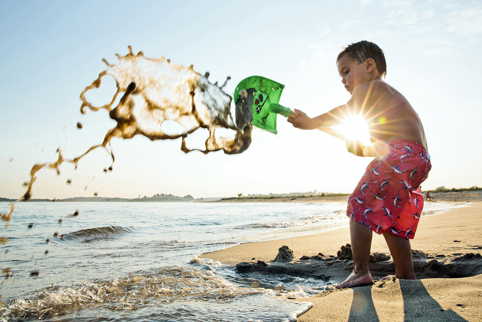 backlit photo of kid shoveling sand and water at the beach by Olivia Gatti