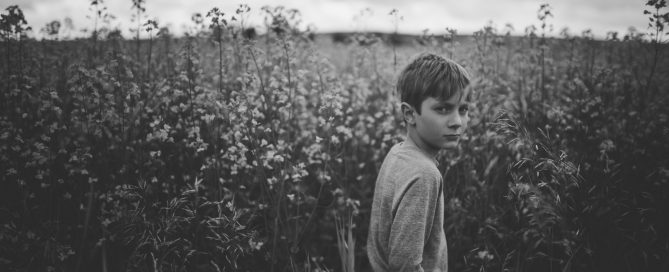 black and white picture of boy in a tall field by Andrea Brooke Photography