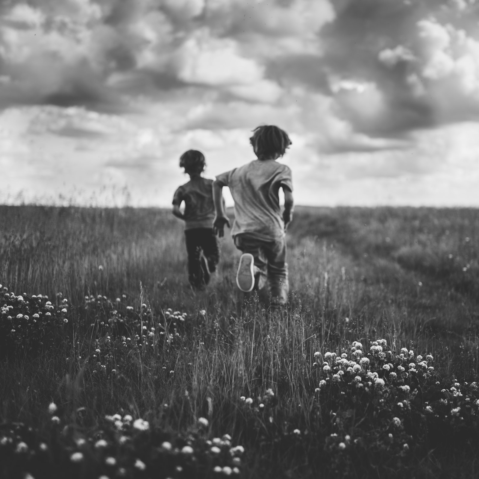 Black and white picture of boys running in a field by andrea brooke photography