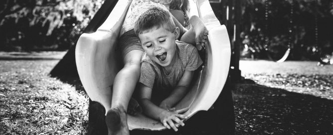 black and white picture of kids sliding down a slide together by Maggie Fuller