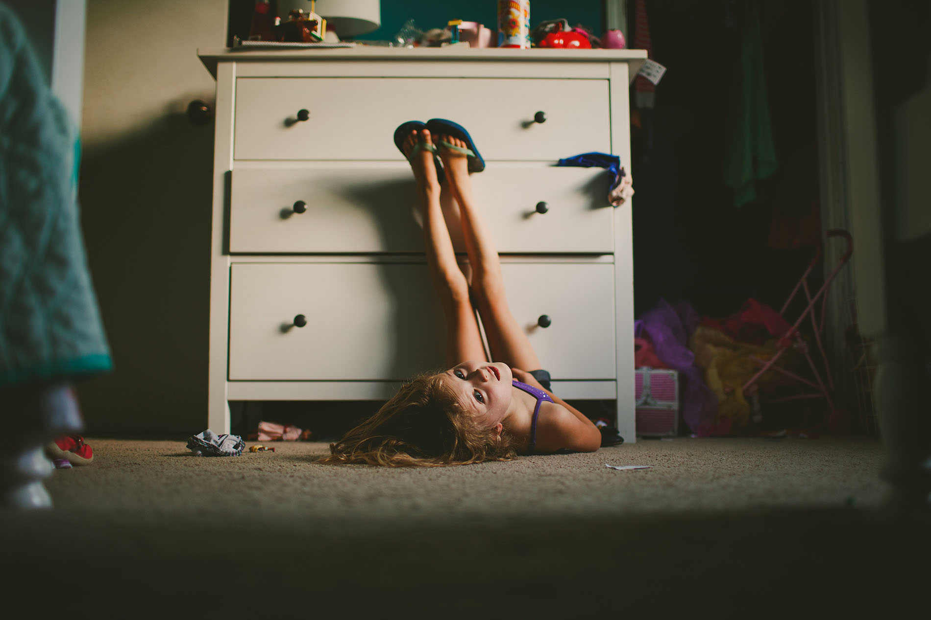 broad light photo of girl laying on her bedroom floor by April Nienhuis