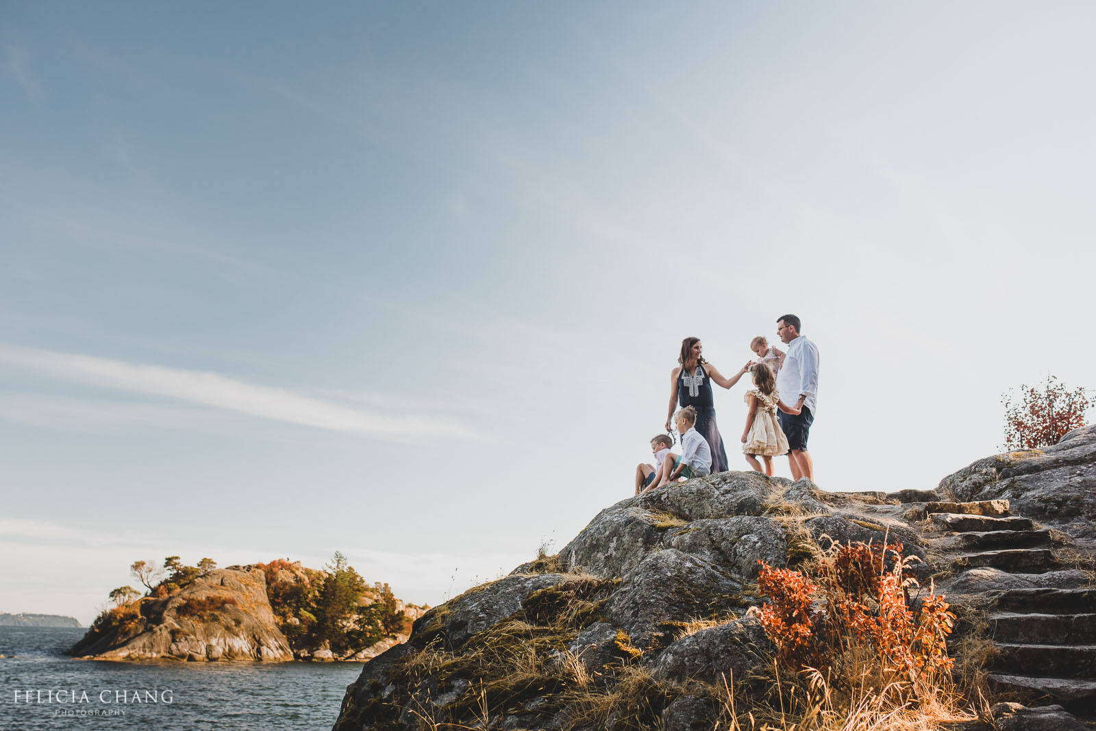family photo on a rock by the water by Felicia Chang