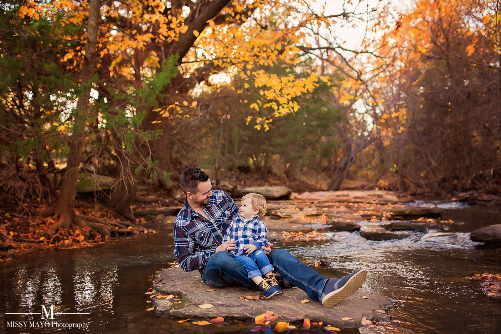 dad laughing with son at a creek during the fall by Missy Mayo